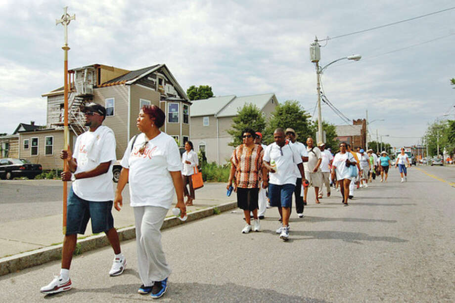 Kevin Profit, pastor with KIngdom Restoration Ministries, and SoNo Alliance chairwoman Corrine Weston lead The SoNo Alliance Prayer Walk Saturday. / (C)2012, The Hour Newspapers, all rights reserved