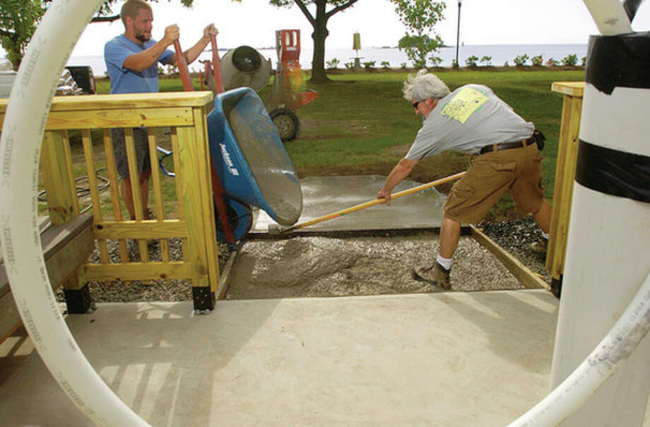 Hour photo / Erik Trautmann Recreation and Parks workers Adam Nesteruk and Steve Green build the new outdoor shower at Calf Pasture Beach Wednesday. / (C)2011, The Hour Newspapers, all rights reserved