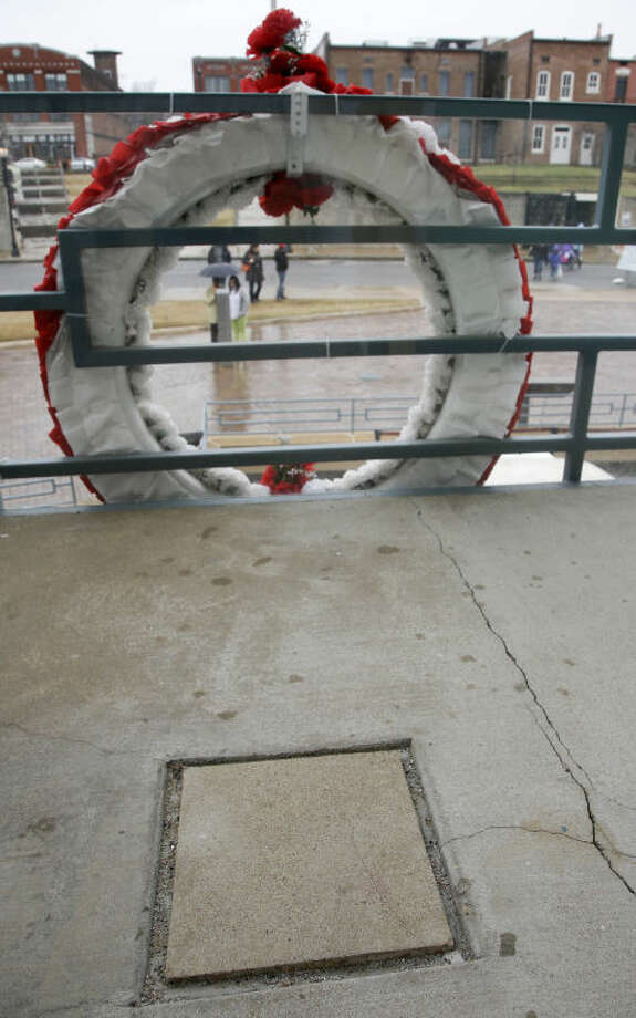 A rectangular piece of the original floor of the Lorraine Motel balcony where Dr. Martin Luther King Jr. was assassinated is seen behind a wreath on Wednesday, April 3, 2013, in Memphis, Tenn. The small window in the upper right hand corner of the building across the street is where the shot was fired that killed King on April 4, 1968, while he in Memphis to support striking sanitation workers. (AP Photo/Mark Humphrey)