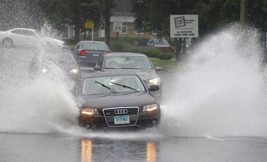 @White=[C] Hour photo / Alex von Kleydorff Heavy rains bring flooding Sunday Motorists on Westport Avenue navigate through and around ponding water on during Sunday's heavy rainfall. / 2011 The Hour Newspapers