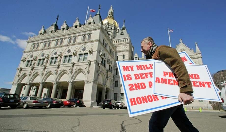 Jody Winslow, of Farmington, Conn., carries signs regarding the second amendment of the U.S. Constitution as he heads back to the Capitol in Hartford, Conn., Wednesday, April 3, 2013. Hundreds of gun rights advocates are gathering at the statehouse in Hartford ahead of a vote in the General Assembly on proposed gun-control legislation. (AP Photo/Charles Krupa) / AP