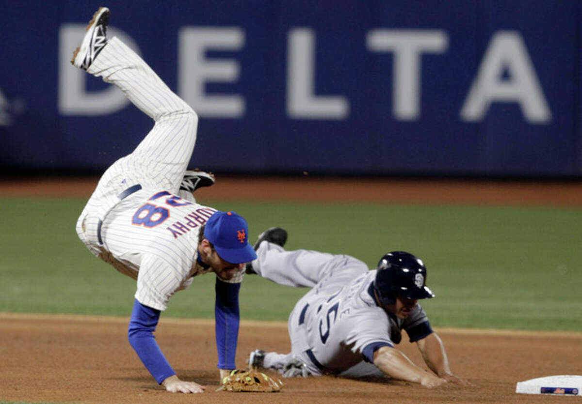 New York Mets second baseman Daniel Murphy flips over San Diego Padres' Will Venable while turning a double play in the fourth inning of a baseball game, Wednesday, April 3, 2013, in New York. Carlos Quentin was out at first. (AP Photo/Mark Lennihan)