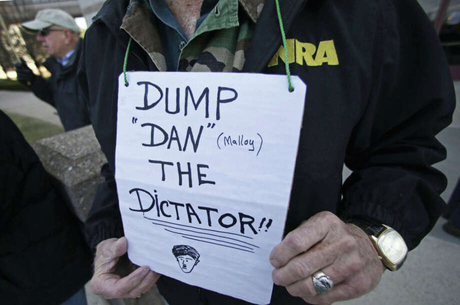 AP photo / Charles KrupaA gun rights advocate holds a sign suggesting the ouster of Gov. Dannel P. Malloy outside the legislative office building at the Capitol in Hartford Wednesday. / AP