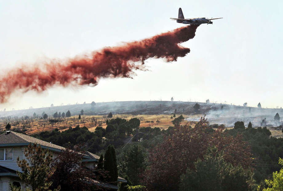 In this Thursday, June 28, 2012 photo, a Bureau of Land Management aerial tanker lays down fire retardant near homes off of Mink Creek Road just south of Pocatello, Idaho. Fire officials say 66 homes and 29 outbuildings in Pocatello have burned in the fast-moving Charlotte fire. (AP Photo/The Idaho State Journal, Doug Lindley) / The Idaho State Journal