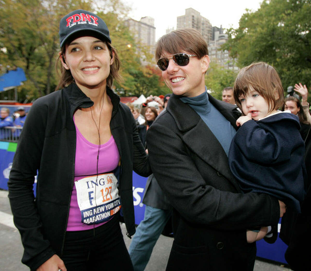 FILE - In this Nov. 4, 2007 file photo, actress Katie Holmes joins her husband Tom Cruise as he holds their daughter Suri after Holmes finished the New York City Marathon in New York. Holmes' attorney Jonathan Wolfe said Friday June 29, 2012 that the couple is divorcing, but called it a private matter for the family. (AP Photo/Kathy Willens, file)