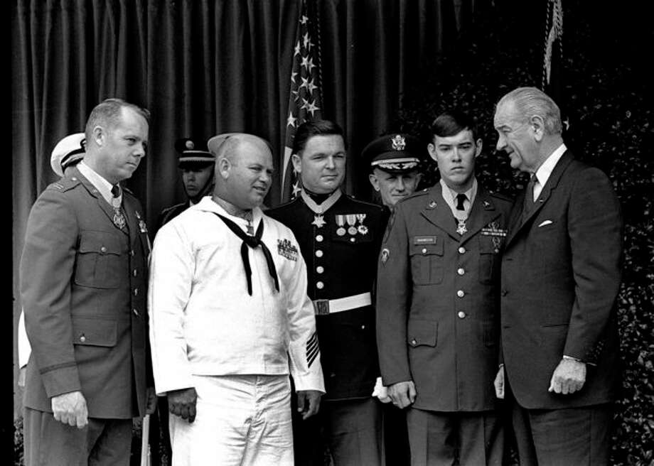 "FILE - In this May 14, 1968 file photo, U.S. President Lyndon Johnson, right, poses at the White House with four winners of the nation's highest award, the Medal of Honor. Decorated for valor in Vietnam, they are, from left: Air Force Capt. Gerald O. Young, of Anacortes, Wash.; Navy Bosn""s Mate James E. Williams, of Rock Hill, S.C.; Marine Sgt. Richard A. Pittman, of Stockton, Calif., and Army Spc. 5 Charles C. Hagmeister, of Lincoln, Neb. Others are unidentified. Pittman and the other recipients can proudly and truthfully say they were awarded the Medal of Honor for their valor in Vietnam. After a recent Supreme Court ruling, anyone else is free under the First Amendment to make the same claim, whether it's true or not. (AP Photo/File) / AP1968"