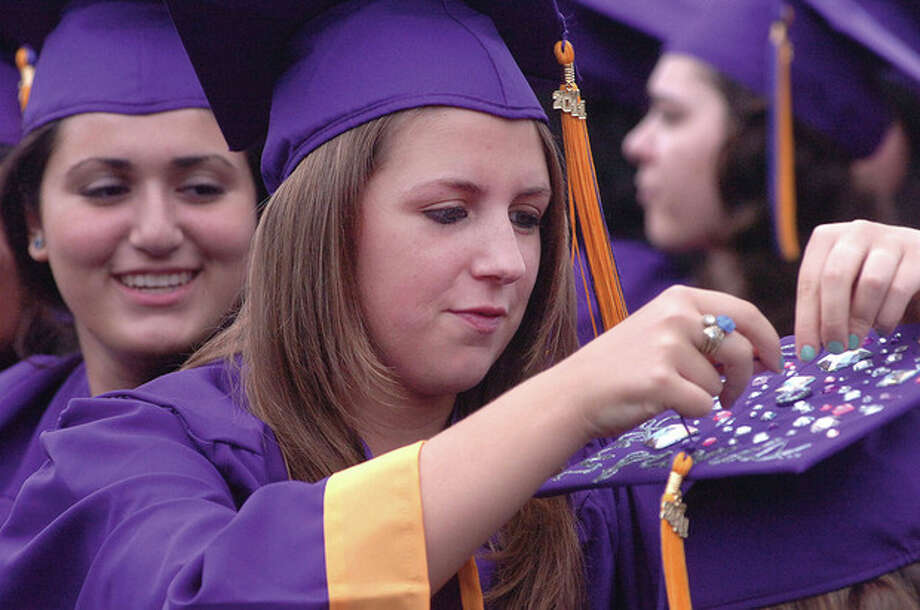 Hour Photo/Alex von Kleydorf. Nicolle Cucco fixes the tassel on her friend mortar board / 2011 The Hour Newspapers