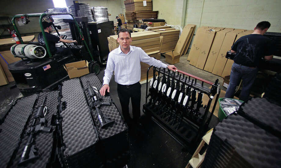 """AP photo / Charles KrupaMark Malkowski, president of Stag Arms, poses as workers move a pallet of rifles for shipment at the Stag Arms company in New Britain Wednesday. Stag Arms, which employs about 230 workers, says its customers are urging it to """"pick up and leave"""" Connecticut. / AP"""