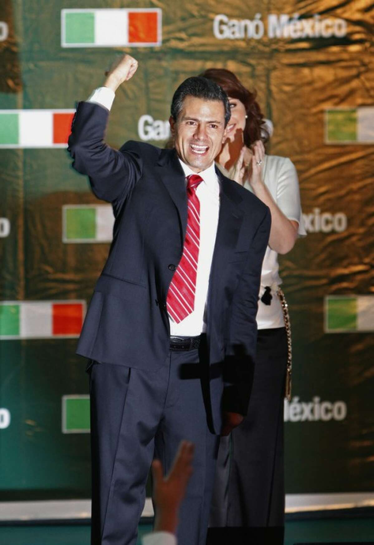 Presidential candidate Enrique Pena Nieto gestures to supporters at his party's headquarters in Mexico City, early Monday, July 2, 2012. Mexico's federal elections institute's preliminary count says Pena Nieto has won the presidency. The candidate for the old-ruling Institutional Revolutionary Party, or PRI, has won about 38 percent of the vote according a representative count of the ballots. (AP Photo/Marco Ugarte)