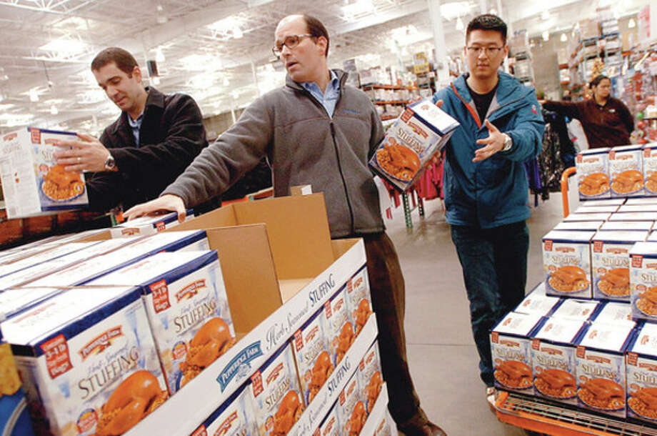 Hour photo / Erik Trautmann Priceline employees Jeff Parise, Eduardo Andrade and Brian Kim load up on stuffing at Costco for Priceline's 7th annual giving. / (C)2011, The Hour Newspapers, all rights reserved