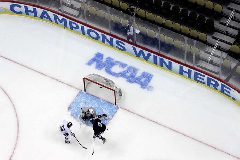 Yale goalie Jeff Malcolm can't stop a shot byYale forward Cody Learned (12) with Yale forward Carson Cooper on defense during an NCAA college hockey practice in Pittsburgh, Wednesday, April 10, 2013. Yale is scheduled to face UMass-Lowell in their Frozen Four game on Thursday. (AP Photo/Gene J. Puskar) / AP