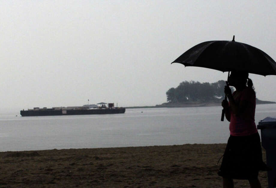Hour Photo / Danielle Robinson A woman with an umbrella trys to stay dry while walking along at Calf Pasture Beach before the annual firework display in Norwalk Sunday afternoon. Hour Photo / Danielle Robinson