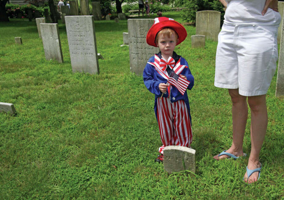 Hour Photo / Danielle Robinson Tristan Meyer-Mitchell, 3, stands by his mom while listening to the cemetery tour given by the Norwalk Historical Society at St. PaulÕs on the Green on Monday afternoon.