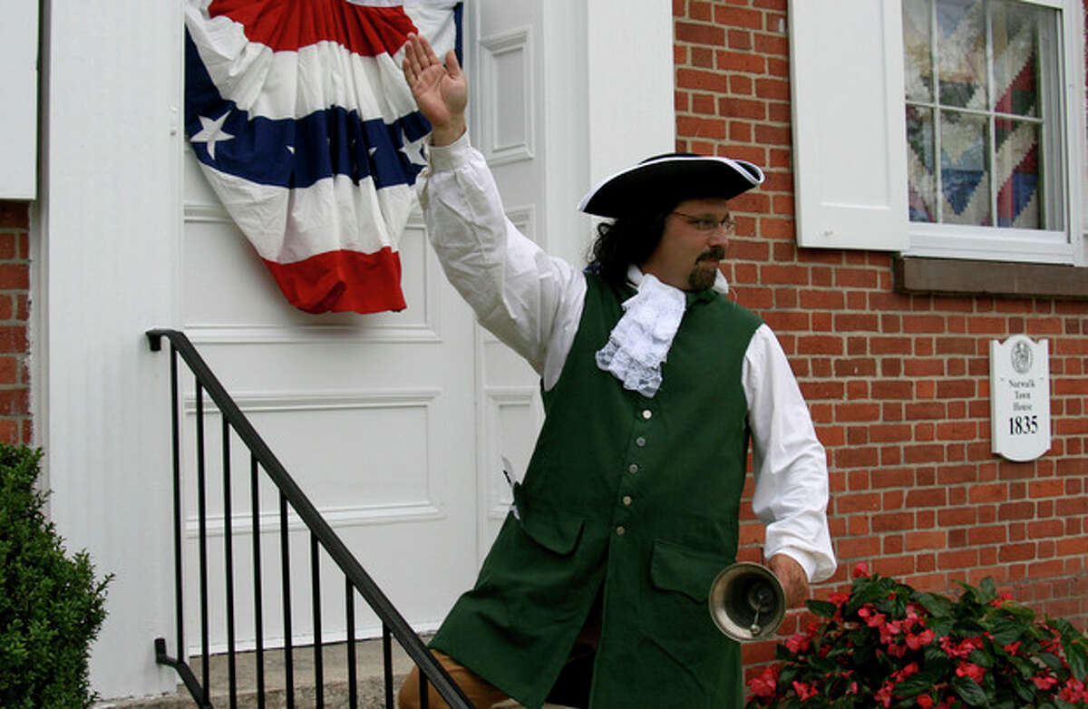 Photo by Chris Bosak Norwalk's Town Clerk Andy Garfunkel dons revolutionary-era garb as he waves to passers-by at historic Mill Hill on Monday.