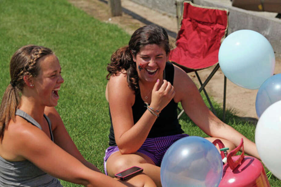 Hour Photo / Danielle Robinson Lindsay Wheeler and Jenn Mscisz laugh as they blow up red white and blue balloons in preparation for the Wilton fireworks Monday afternoon.