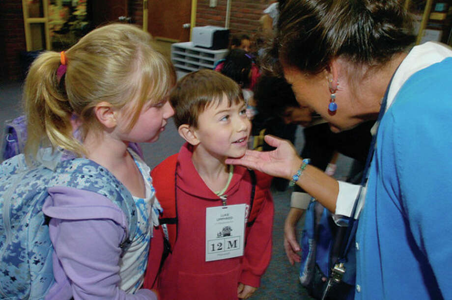 Miller Driscoll School students Katie and Luke Umphred are greeted by teacher Lynn Tyler on the first day of school Tuesday. / (C)2011, The Hour Newspapers, all rights reserved