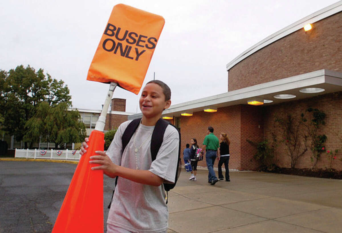 West Rocks Middle School student Luis Betances prepares the school's driveway for buses on the first day of school Tuesday.