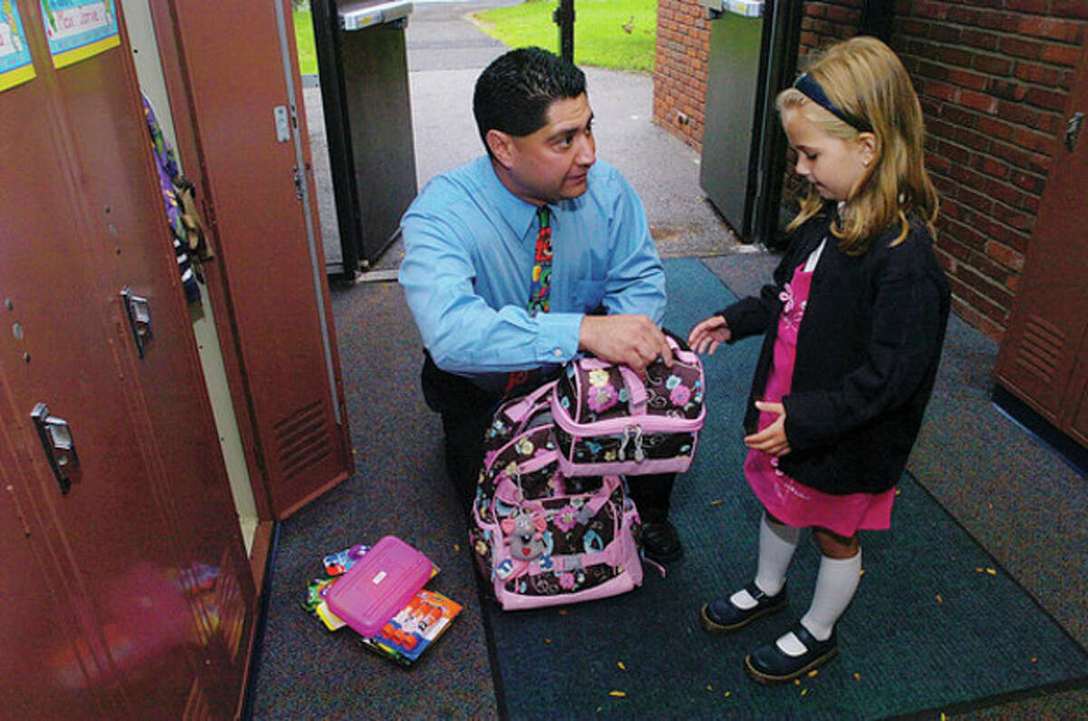 Miller Driscoll School kindergarten teacher Sal Giaimo helps Melanie Rutkowski find her locker on the first day of school Tuesday.