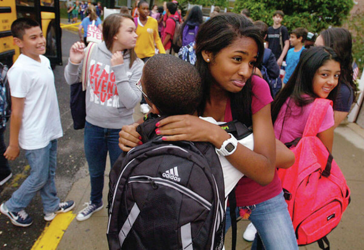 West Rocks Middle School 8th graders Charlene Atkinson and Robens Opont greet each other on the first day of school Tuesday.
