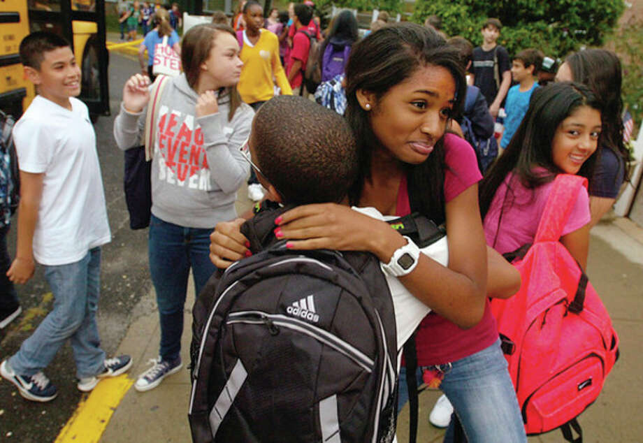 West Rocks Middle School 8th graders Charlene Atkinson and Robens Opont greet each other on the first day of school Tuesday. Hour photo / Erik Trautmann / (C)2011, The Hour Newspapers, all rights reserved