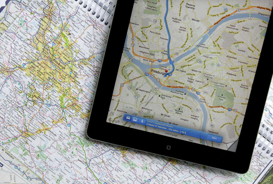 In this Tuesday, May 8, 2012 photo a traditional road map of the Pittsburgh area and one showing the same region on an iPad are seen placed together in Moreland Hills, Ohio. Transportation agencies around the country are printing fewer maps to cut costs or just to acknowledge that public demand is down. (AP Photo/Amy Sancetta) / AP