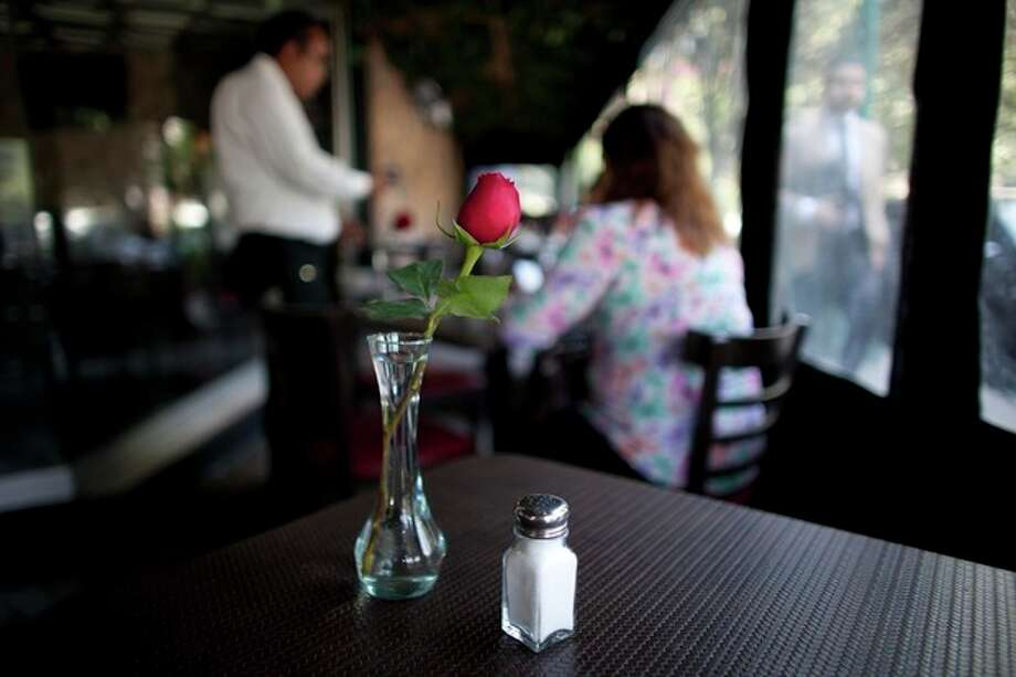 "In this April 9, 2013 photo, a salt shaker sits on a table in a restaurant in Mexico City. The country's Health Secretary Armando Ahued launched a campaign, dubbed ""Less Salt, More Health,"" to get restaurants to take salt shakers off their tables. Officials and the city's restaurant chamber signed an agreement to encourage eateries to provide shakers only if guests ask for them. The program is voluntary but the chamber is urging its members to comply. (AP Photo/Alexandre Meneghini) / AP"