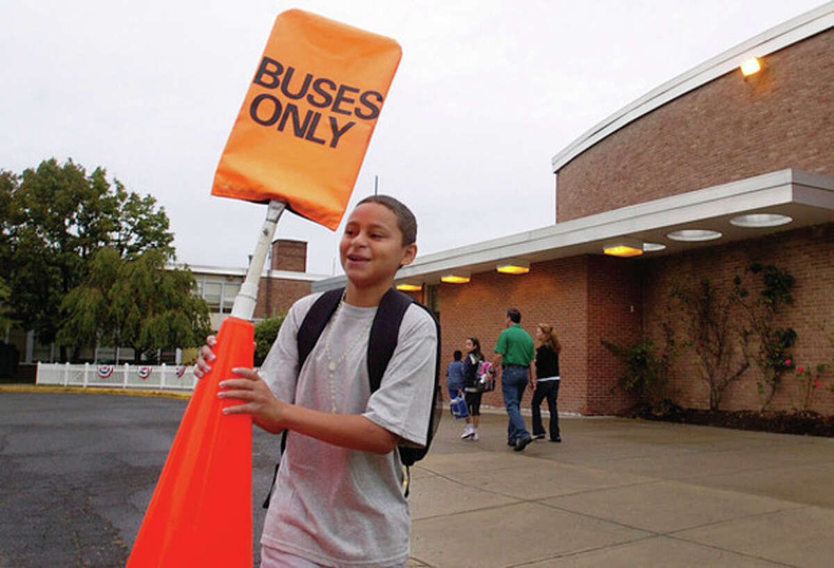 West Rocks Middle School student Luis Betances prepares the school's driveway for buses on the first day of school Tuesday. Hour photo / Erik Trautmann