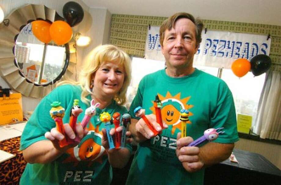 Photo/Alex von Kleydorff. Organizer Richard Belyski and Mary Hoethke show some of their personal favorite Pez dispensers at the Annual Northeast Pez Collectors Gathering in Stamford