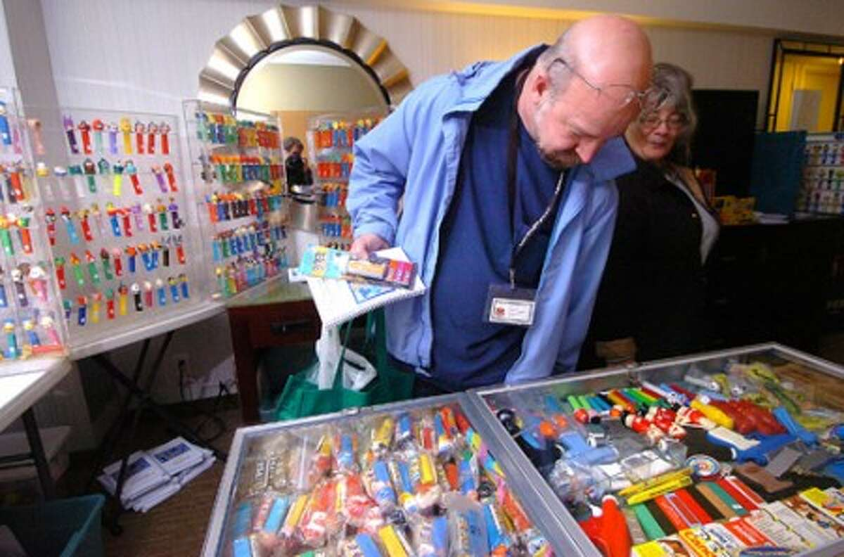 Photo/Alex von Kleydorff. Jason Brennan from Otisville NY looks over some of the cases filled with Pez dispensers.