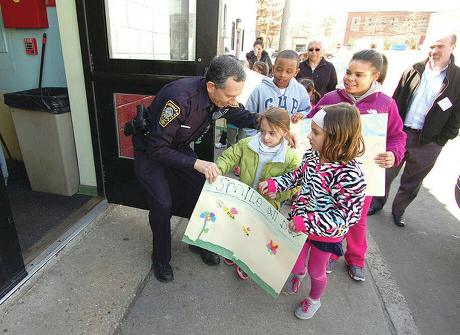 Hour photo / Alex von KleydorffWith a police cruiser full of food collected by the children, officer Cesar Ramirez holds open the door to the shelter for kids who made signs and walked from Columbus Magnet school to donate the food. / 2013 The Hour Newspapers