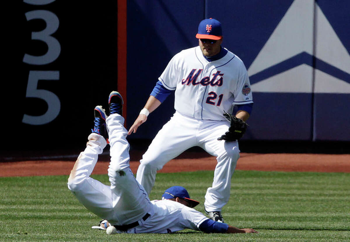 New York Mets shortstop Ruben Tejada, front, can't get to a fly ball hit by San Diego Padres' Will Venable as left fielder Lucas Duda backs up the play during the fourth inning of a baseball game, Thursday, April 4, 2013, at Citi Field in New York. (AP Photo/Mark Lennihan)