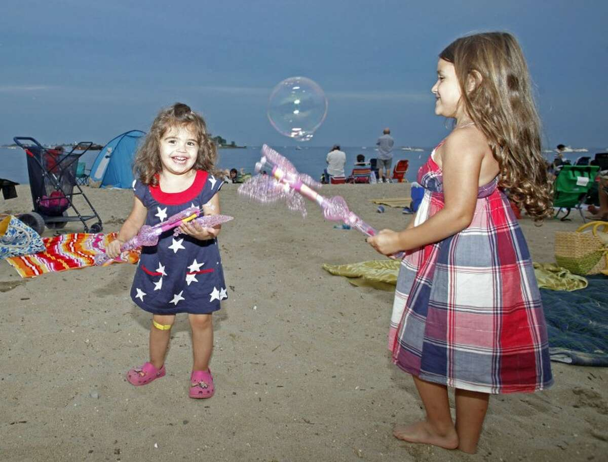 Lucy Karimi, 2, and her sister Lola, 4, play with toys on Calf Pasture Beach during Norwalk's annual firework display Tuesday evening. Hour Photo / Danielle Robinson