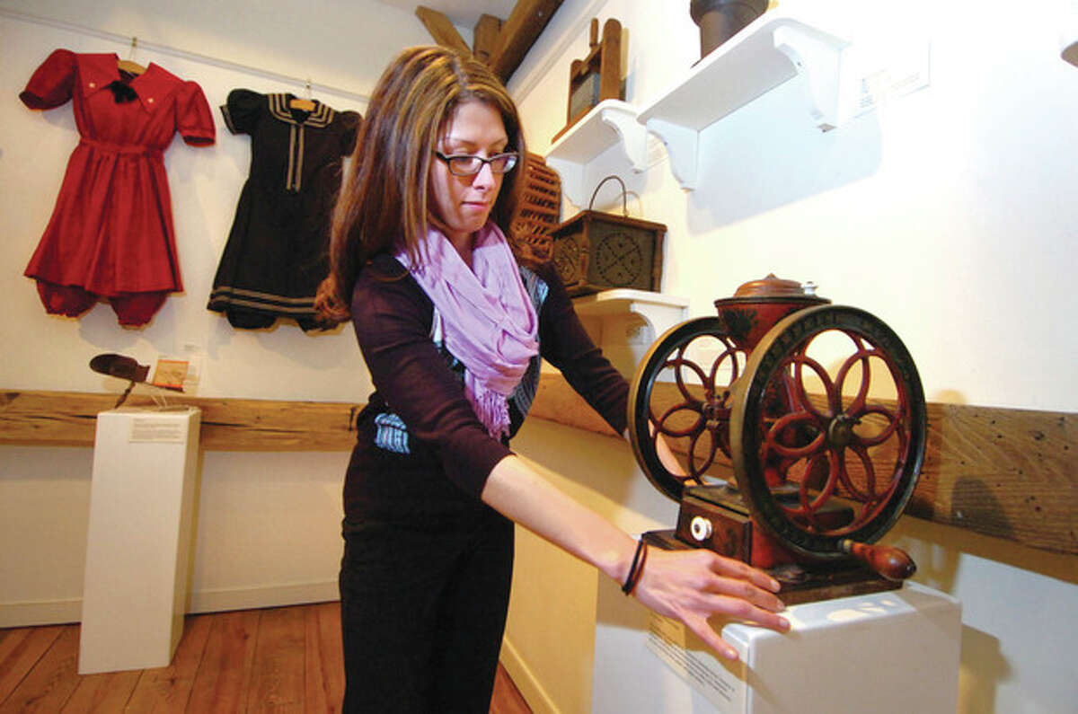 Hour Photo/Alex von Kleydorff . For the exhibit 75 Objects 75 Years at the Wilton Historical Society, Education and Program Coordinator Katherine Chacon straightens one of the displays, a coffee Grinder made in 1873 from Philadelphia.