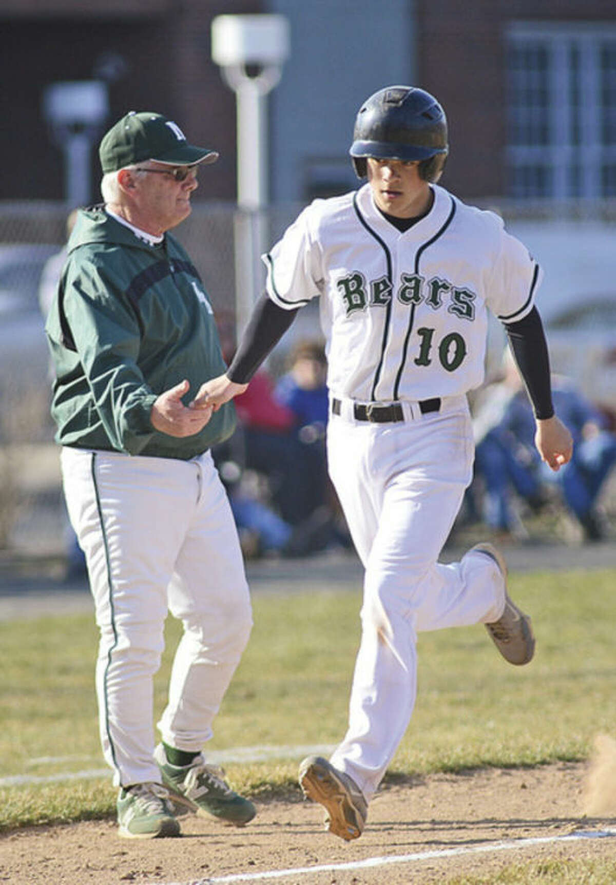 Hour photo/Erik Trautmann Norwalk's Dave Balunek slaps hands with head coach Pete Tucci as he rounds third after hitting a solo home run during Friday's game against Danbury at Malmquist Field. It was the only run Norwalk would get in an 8-1 loss.