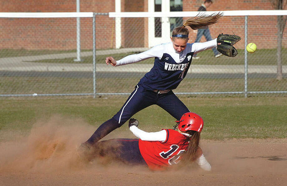 Hour Photo/Alex von KleydorffThe ball gets away from Staples shortstop Nikki Bukovsky after tagging McMahon's Natalie Leslie to end the third inning of Friday's game. Leslie was called out. Staples won, 12-11. / 2013 The Hour Newspapers