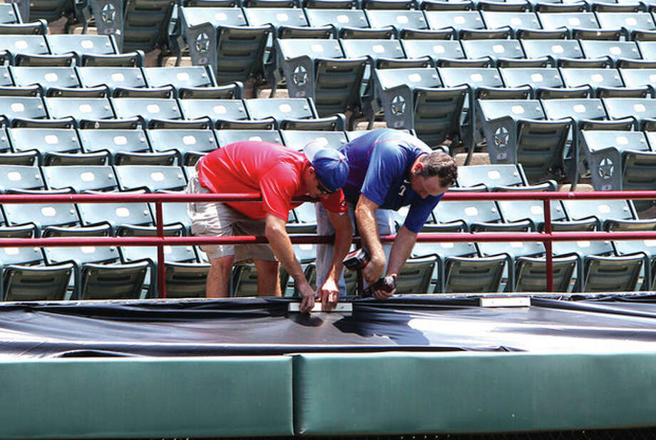 AP photo Workers fasten a tarp over the area where Shannon Stone fell at the Texas Rangers Ballpark in Arlington, Texas. Stone tumbled over a railing and plunged 20 feet onto concrete below while catching a ball Thursday night, and died at a hospital a short time later, the medical examinerÕs office said. / AP