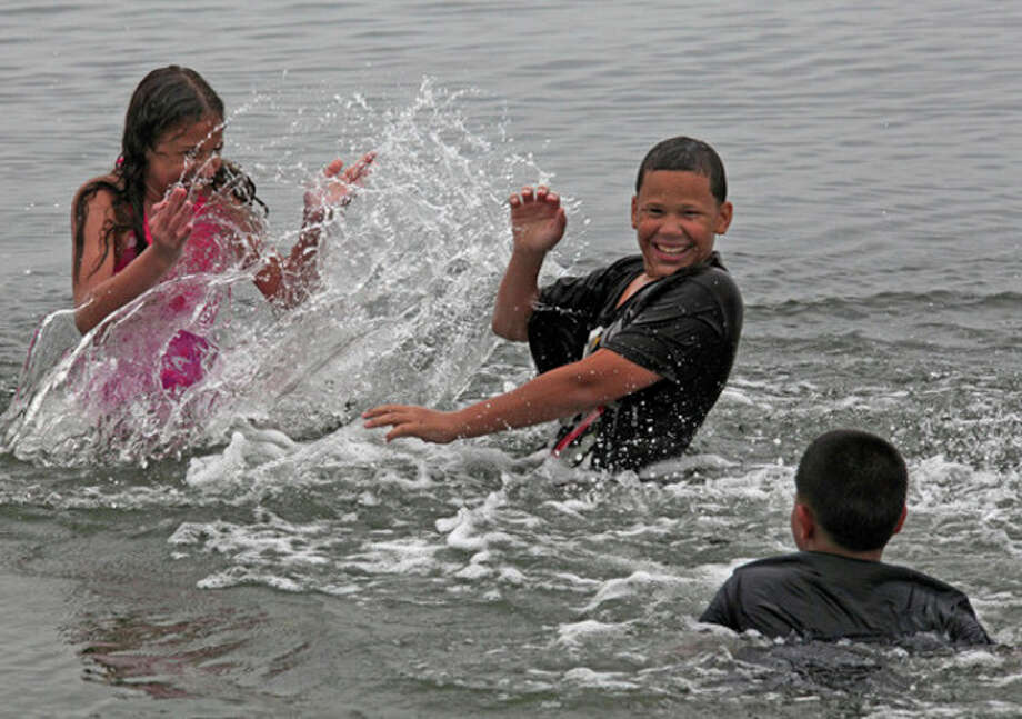 Kiaraly Olavarria, 10, Joey Olavarria, 13 and Robert Soto, 11, play in the water at Calf Pasture Beach in Norwalk Sunday afternoon despite the rain. Hour Photo / Danielle Robinson