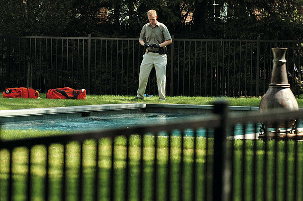 Darien police investigate the scene at 2 Mansfield Place where a person was found floating in the swimming pool there Wednesday. Hour photo / Erik Trautmann