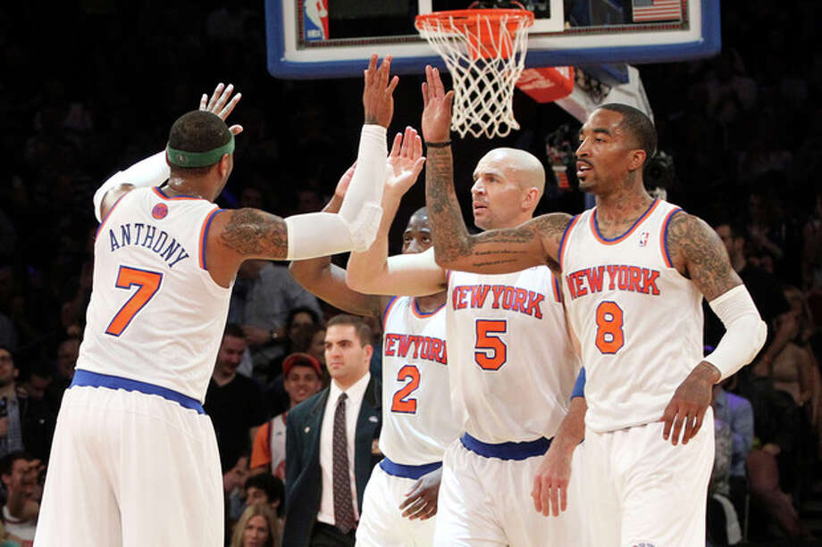 New York Knicks' Carmelo Anthony (7) high fives team mates Raymond Felton (2) Jason Kidd (5) and J.R. Smith (8) during the first half of an NBA basketball game against the Washington Wizards, Tuesday, April 9, 2013, at Madison Square Garden in New York. (AP Photo/Mary Altaffer) / AP