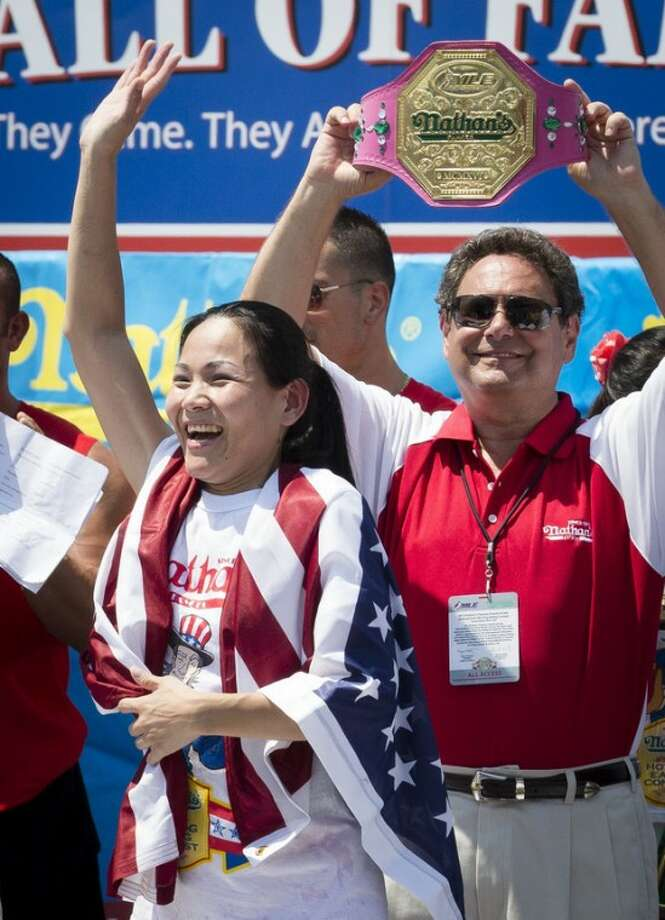 "Sonya ""The Black Widow"" Thomas accepts her trophy after she wins Nathan's Famous Women's Hot Dog Eating World Championship, Wednesday, July 4, 2012, at Coney Island, in the Brooklyn borough of New York. Thomas beat her own record by gobbling down 45 hot dogs and buns in 10 minutes to win the women's competition at the annual Coney Island contest. (AP Photo/John Minchillo)"
