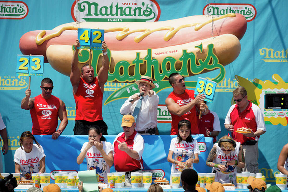 Competitors at Nathan's Famous Women's Hot Dog Eating World Championship gorge themselves against the clock, Wednesday, July 4, 2012, at Coney Island, in the Brooklyn borough of New York. Sonya Thomas beat her own record by gobbling down 45 hot dogs and buns in 10 minutes to win the women's competition at the annual Coney Island contest. (AP Photo/John Minchillo)