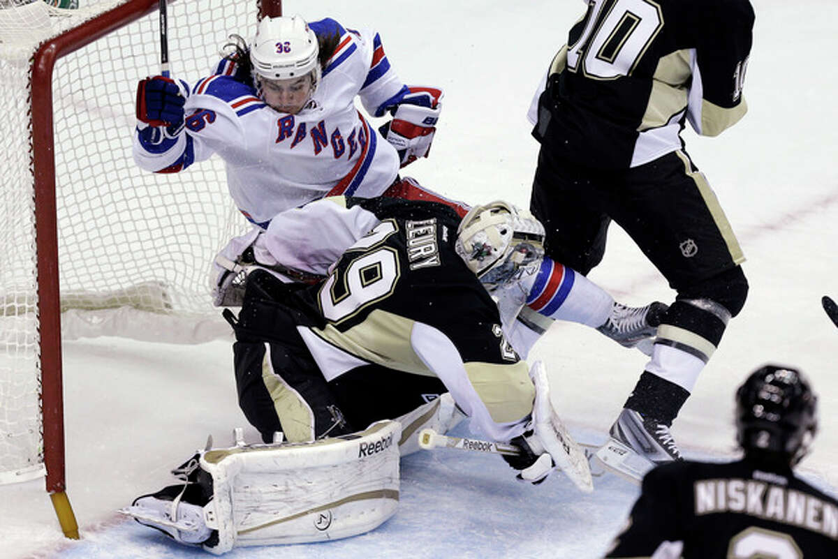 New York Rangers right wing Mats Zuccarello (36) collides with Pittsburgh Penguins goalie Marc-Andre Fleury (29) during the first period of an NHL hockey game in Pittsburgh on Friday, April 5, 2013. (AP Photo/Gene J. Puskar)