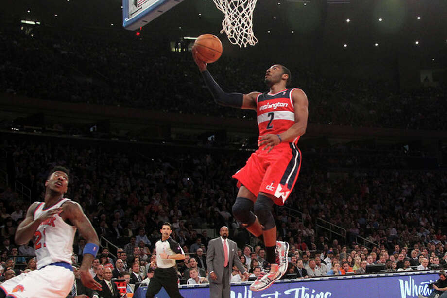 Washington Wizards' John Wall (2) scores as New York Knicks' Iman Shumpert looks on during the first half of an NBA basketball game, Tuesday, April 9, 2013, at Madison Square Garden in New York. (AP Photo/Mary Altaffer) / AP