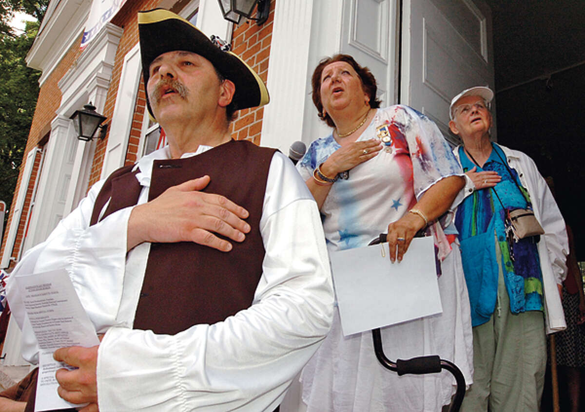 Ed Echkert, Pat Rubino and Leona Lepofsky say the national anthem during The Norwalk Historical Society's Independence Day celebration Wednesday at Mill Hill Historic Park. Hour photo / Erik Trautmann