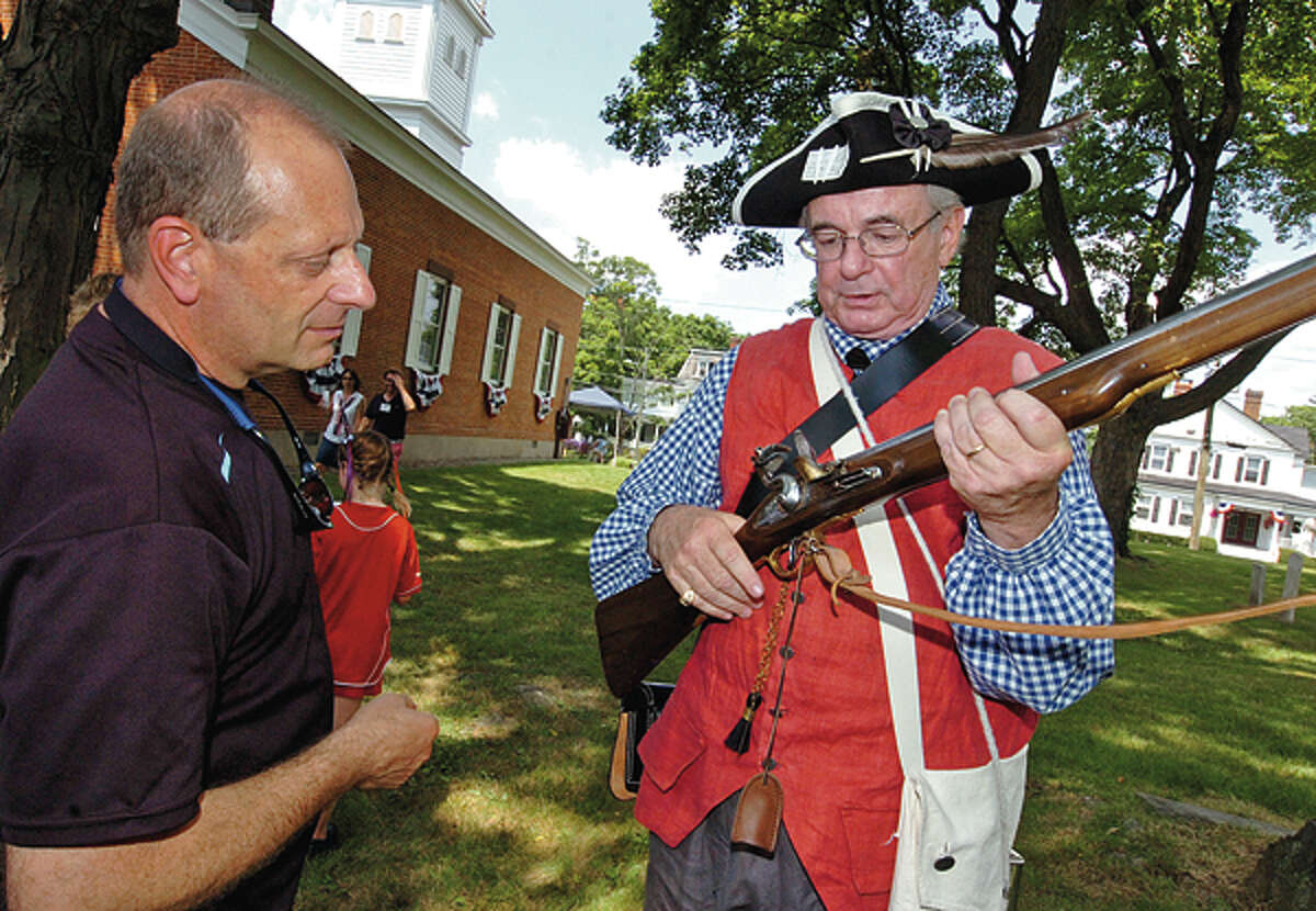 Emil Albanese talks with Bob Lasprogato of Sons of the American Revolution about his musket during The Norwalk Historical Society's Independence Day celebration Wednesday at Mill Hill Historic Park. Hour photo / Erik Trautmann