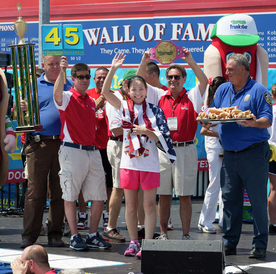 """Sonya """"The Black Widow"""" Thomas accepts her trophy after she wins Nathan's Famous Women's Hot Dog Eating World Championship, Wednesday, July 4, 2012, at Coney Island, in the Brooklyn borough of New York. Thomas beat her own record by gobbling down 45 hot dogs and buns in 10 minutes to win the women's competition at the annual Coney Island contest. (AP Photo/John Minchillo) / AP"""