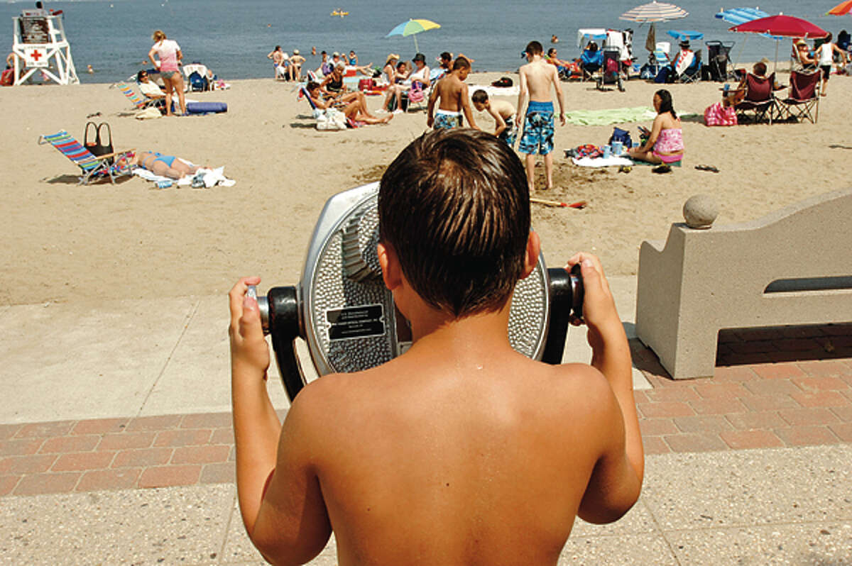 A youg boy surveys the scene of people celebrating the 4th at Calf Pasture Beach Wednesday. Hour photo / Erik Trautmann