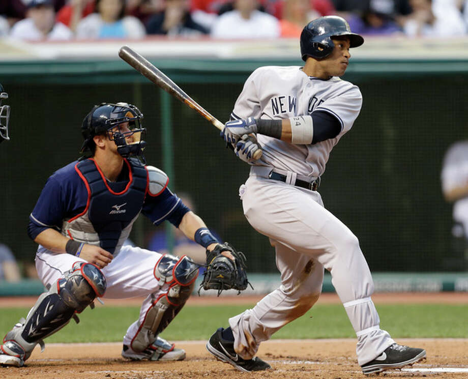 New York Yankees' Robinson Cano watches his two-run double off Cleveland Indians starting pitcher Carlos Carrasco in the second inning of a baseball game, Tuesday, April 9, 2013, in Cleveland. Indians catcher Yan Gomes is at left. (AP Photo/Tony Dejak) / AP