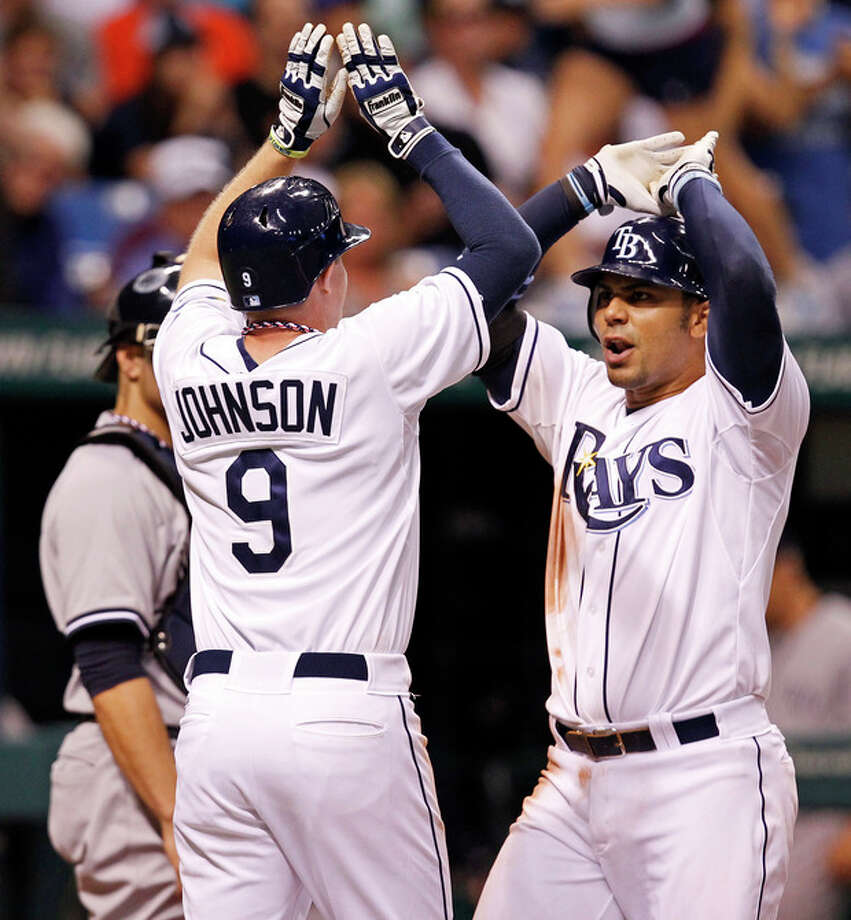 Tampa Bay Rays' Carlos Pena, right, is congratulated by Elliot Johnson after his two-run home run scored both during the seventh inning of a baseball game against the New York Yankees, Wednesday, July 4, 2012, in St. Petersburg, Fla. (AP Photo/Mike Carlson) / FR155492 AP