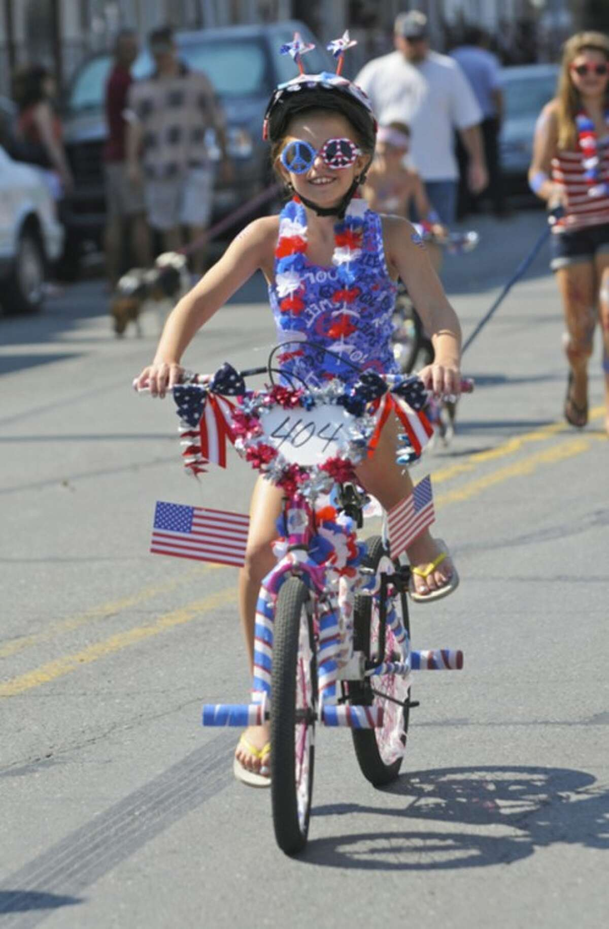 """Brianna Honis participates in the Port Carbon Citizens Committee's annual Fourth of July Parade nicknamed the """"Baby Parade"""" in Port Carbon, Pa. Wednesday, July 4, 2012. (AP Photo/Republican-Herald, Jacqueline Dormer)"""
